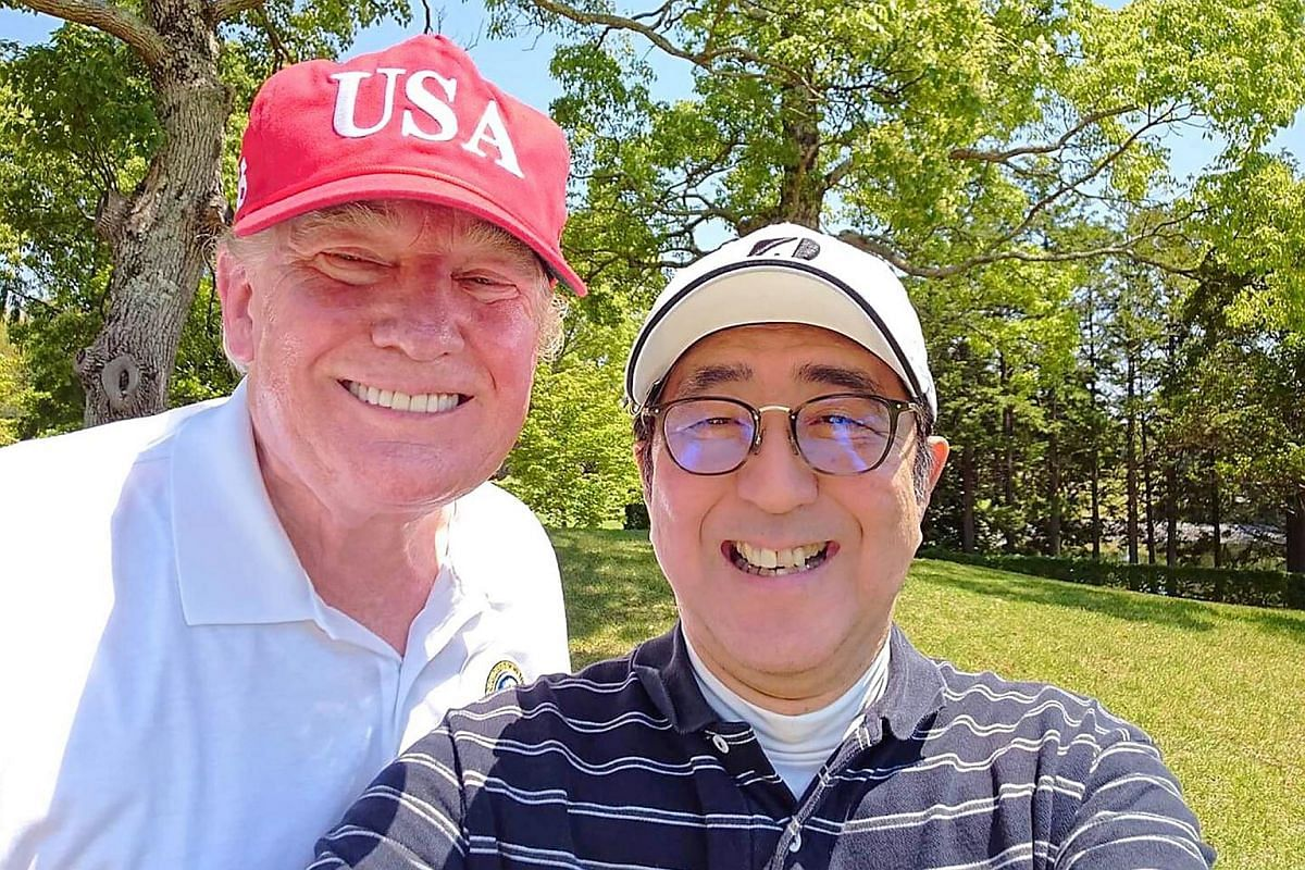 US President Donald Trump and Japanese Prime Minister Shinzo Abe pose for a photograph while playing a round of golf at Mobara Country Club in Chiba.