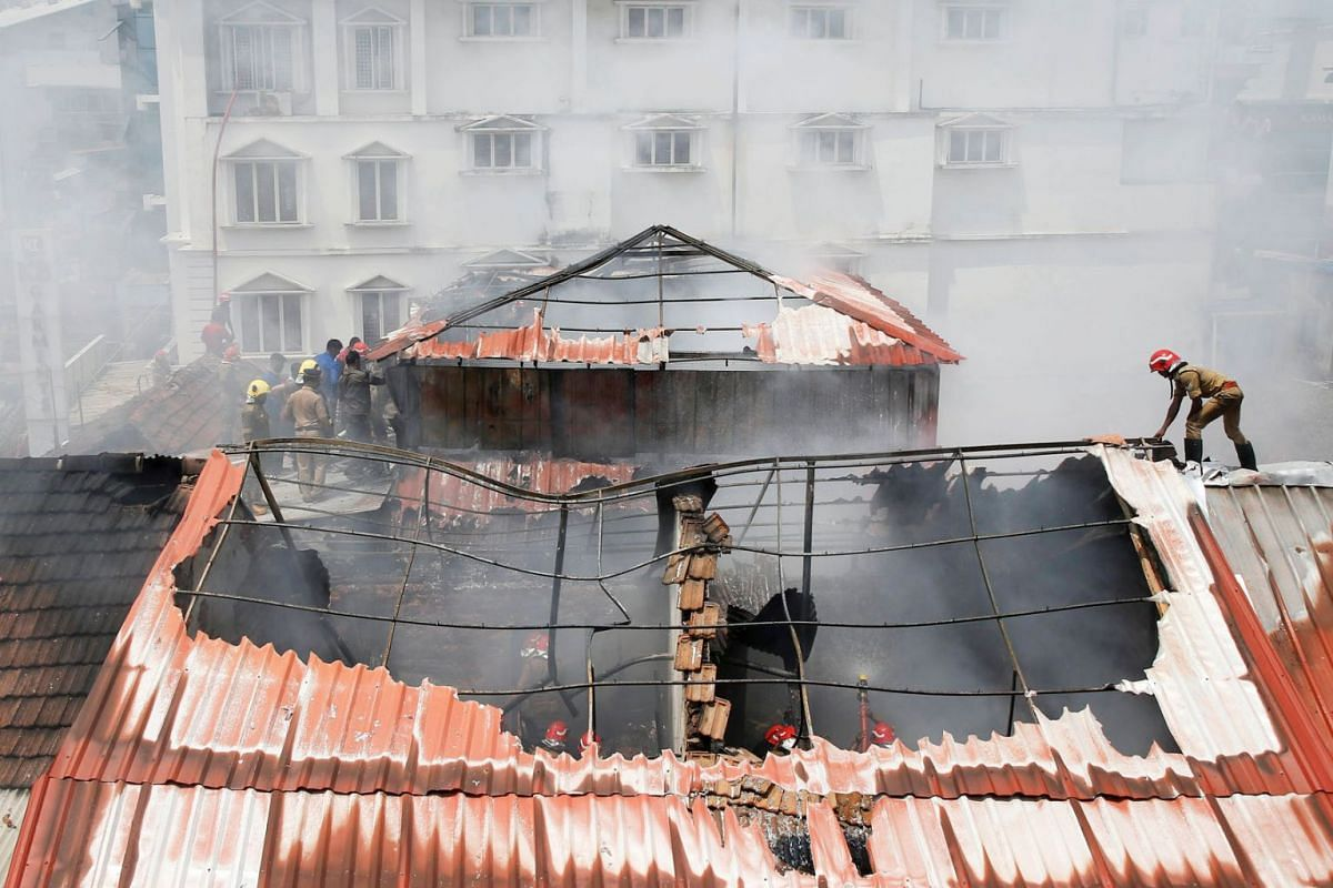 A firefighter walks on the rooftop as others try to douse a fire that broke out at a wholesale market in Kochi, India, May 27, 2019. REUTERS