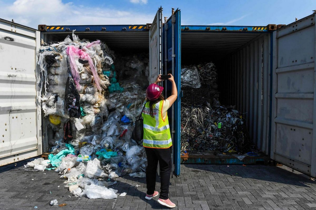 A member of the media takes pictures of containers filled with plastic waste before shipping back to the country of origin in Port Klang, west of Kuala Lumpur on May 28, 2019. PHOTO: AFP