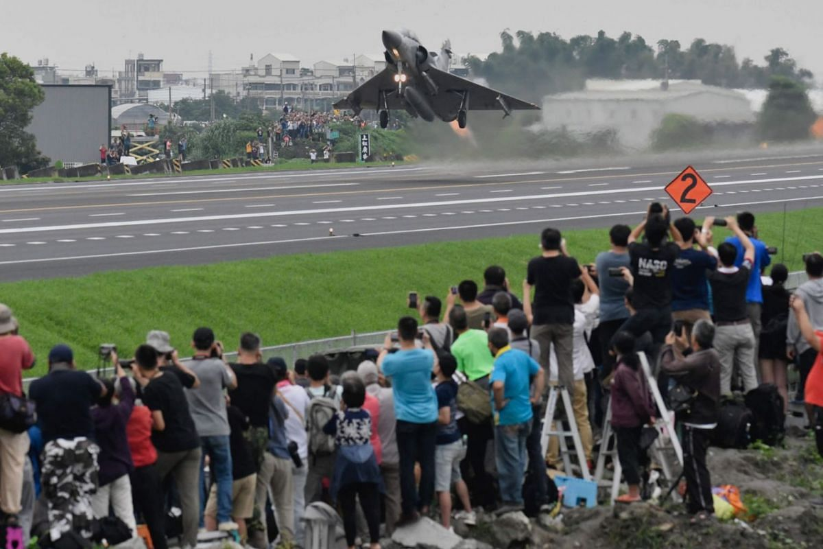 A French-made Mirage fighter jet takes off from the freeway in Changhua county, central Taiwan, as local air fans take photos during the 35th Han Kuang drill on May 28, 2019.  PHOTO: AFP