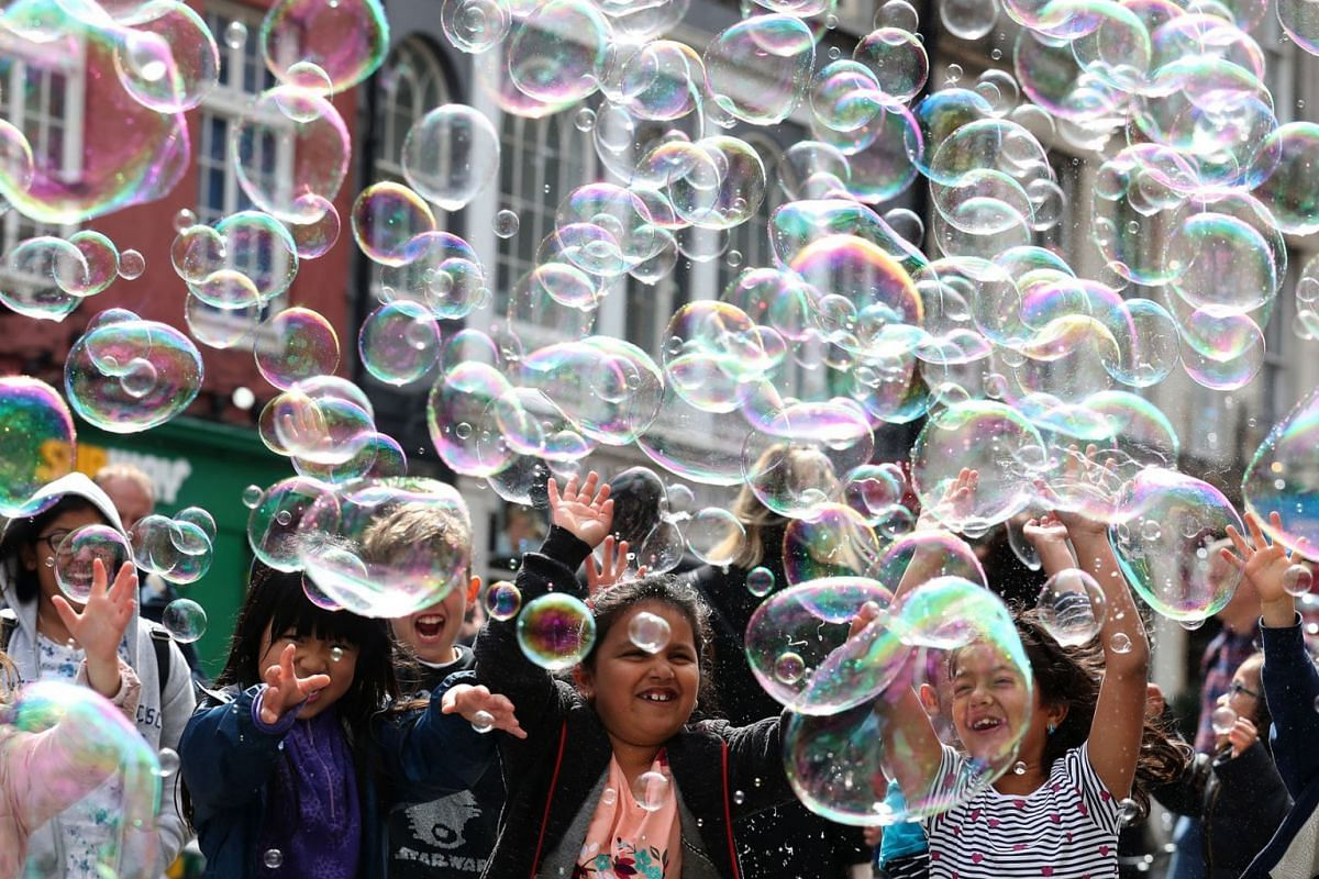Children try to catch soap bubbles created by a street artist during the holiday festivities along the Royal Mile, 27 May 2019, Edinburgh, Scotland. PHOTO: PA WIRE VIA DPA