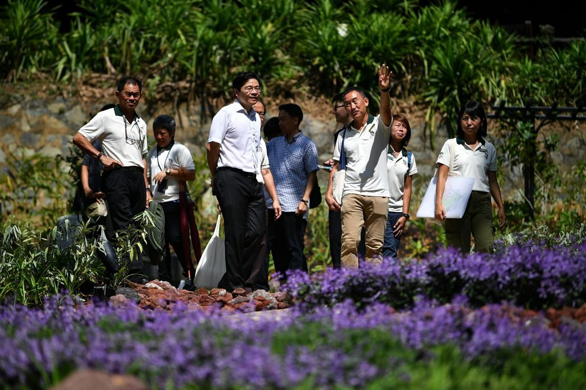 NParks director, Fort Canning Park, Mr Koh Poo Kiong (foreground, right) giving Minister for National Development Lawrence Wong (foreground, left), the guest of honour, a tour of the Spice Garden.