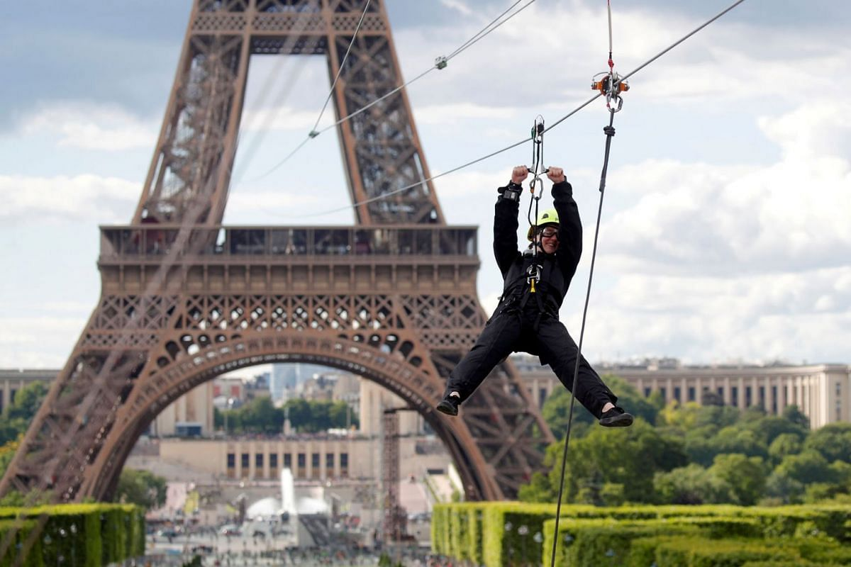 A participant rides a zip line from the second floor of the Eiffel Tower, 115m above ground along an 800m long route, as part of the Smash Perrier free event operating until June 2 in Paris, France, May 28, 2019. PHOTO: REUTERS