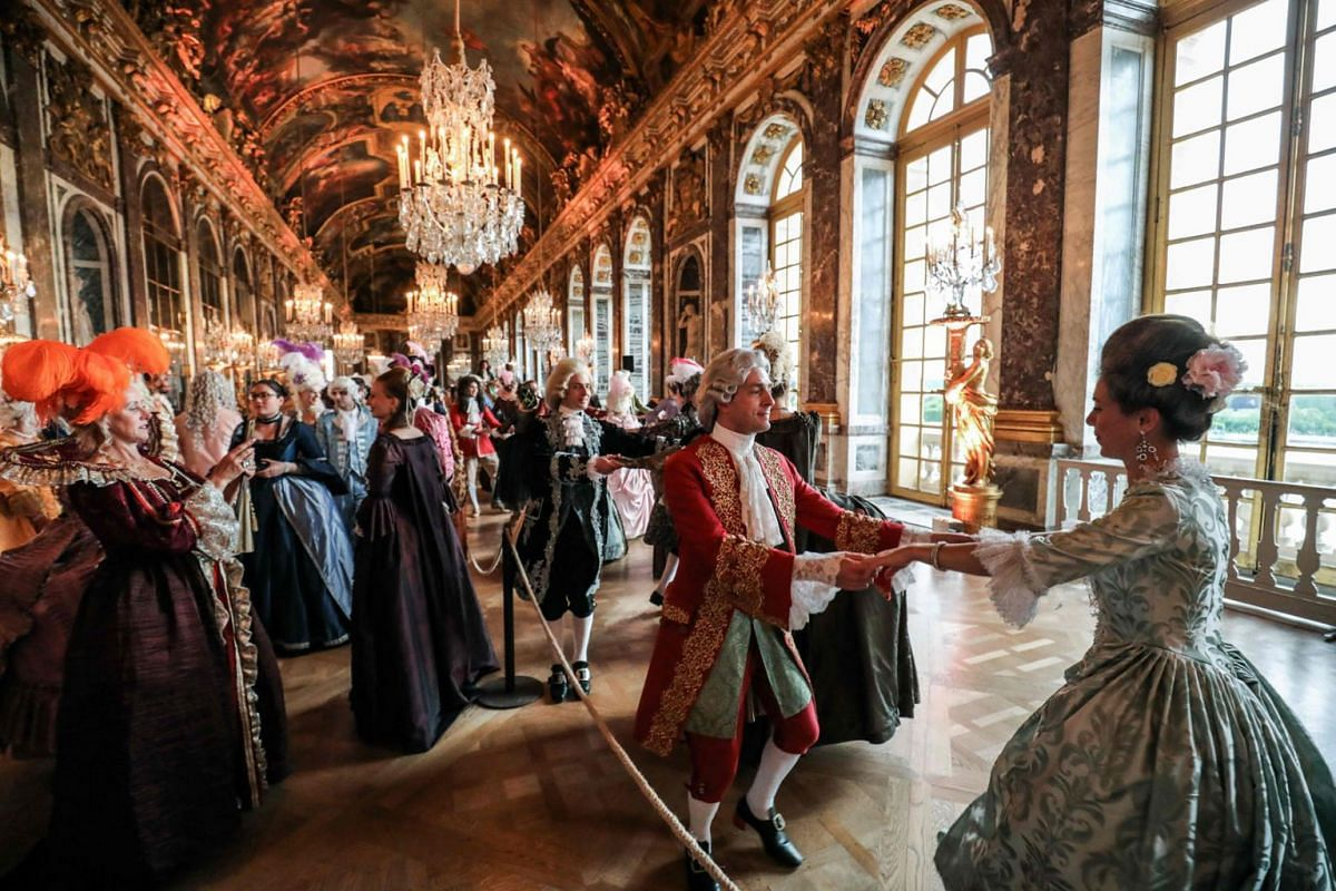 "People in period costume dance as they take part in the ""Fetes Galantes"" fancy dress evening at the Galerie des Glaces (Hall of Mirrors) in Chateau de Versailles on May 27, 2019. PHOTO: AFP"
