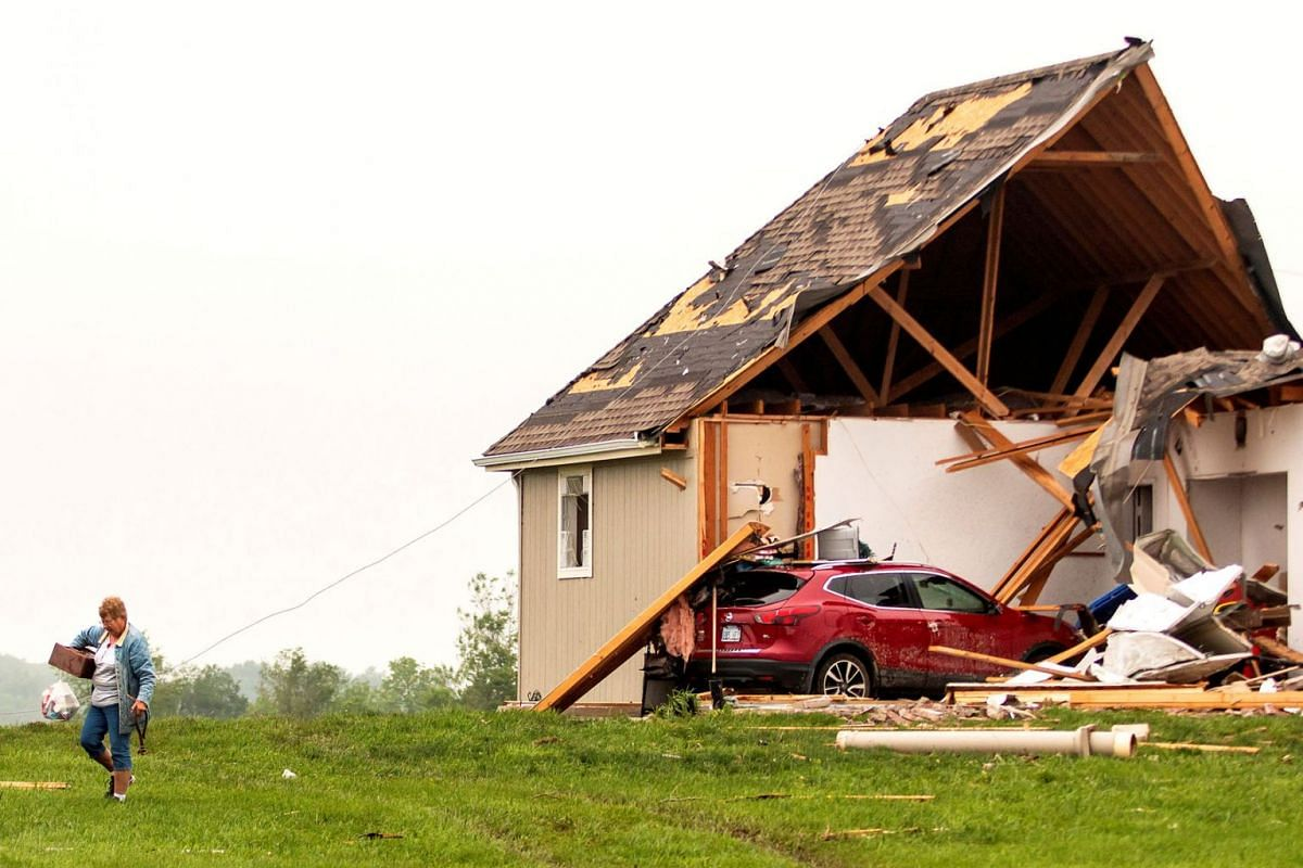A woman walks away from a damaged house after several tornadoes reportedly touched down, in Linwood, Kansas, U.S., May 29, 2019. PHOTO: REUTERS