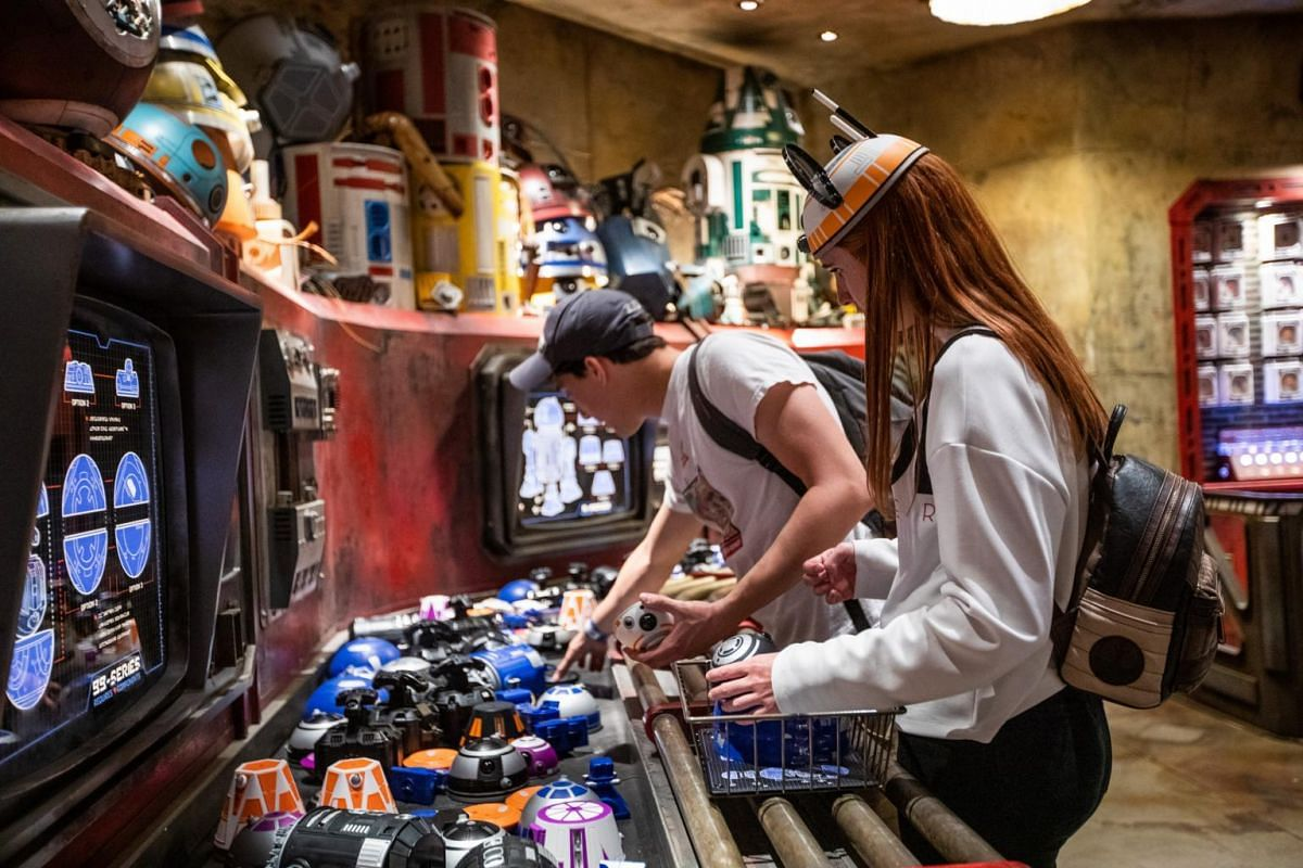 Guests pick parts from a conveyor belt to build a robotic sidekick inside the Droid Depot at the new Star Wars: Galaxy's Edge expansion at Disneyland Park in Anaheim, California.