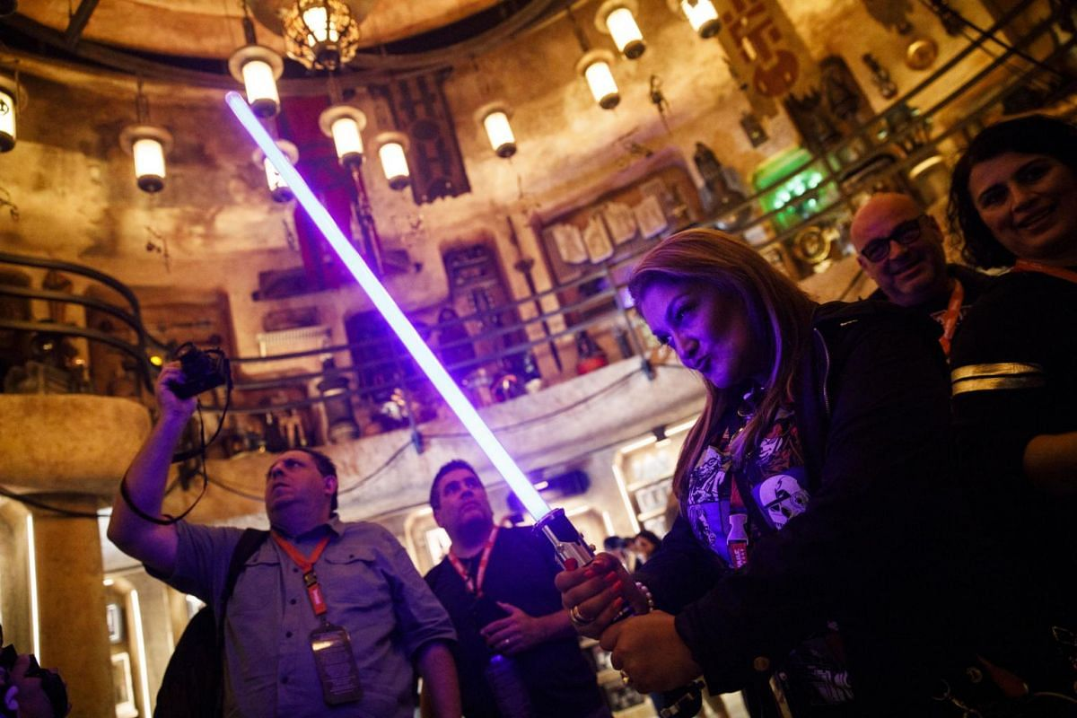 A visitor holds a lightsaber inside Dok-Ondar's Den of Antiquities at the Star Wars: Galaxy's Edge at the Disneyland theme park in Anaheim, California.