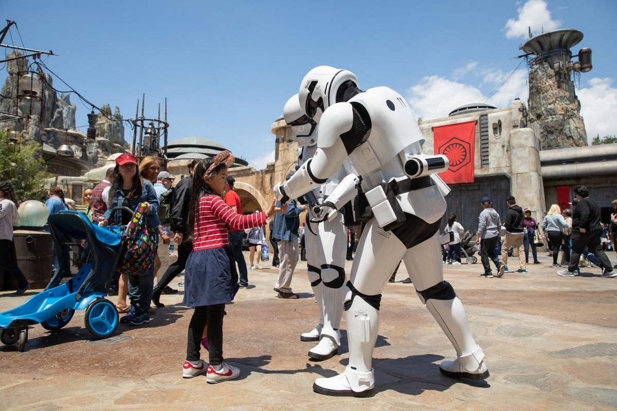 Stormtroopers interact with a guest at the new Star Wars: Galaxy's Edge expansion at Disneyland Park in Anaheim, California.