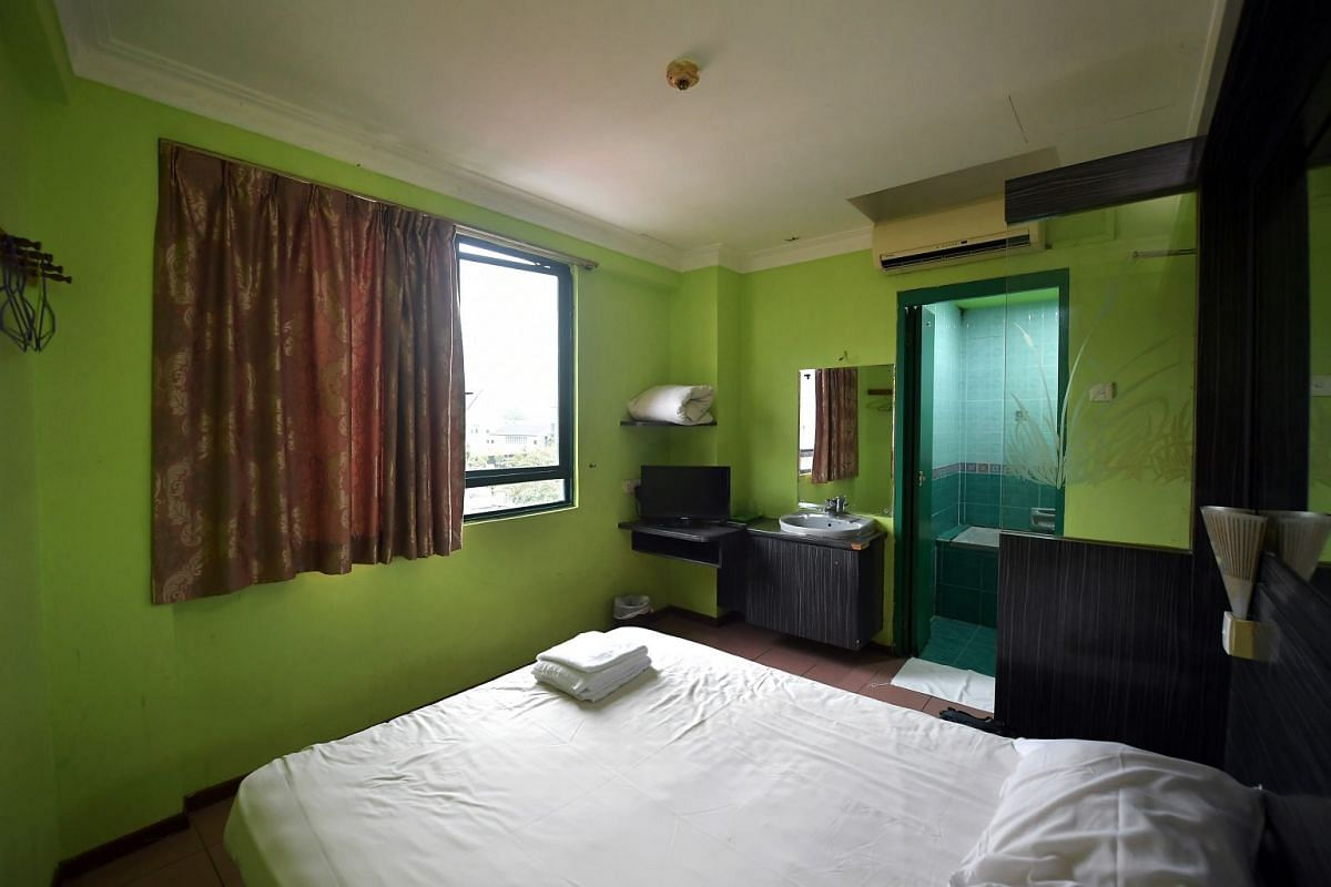 The room decor (above) is functional, if dated, the bedside lamps are dusty and the bed sheet is pockmarked with cigarette-butt burn-holes. Toilet paper, a kettle and cups are provided.