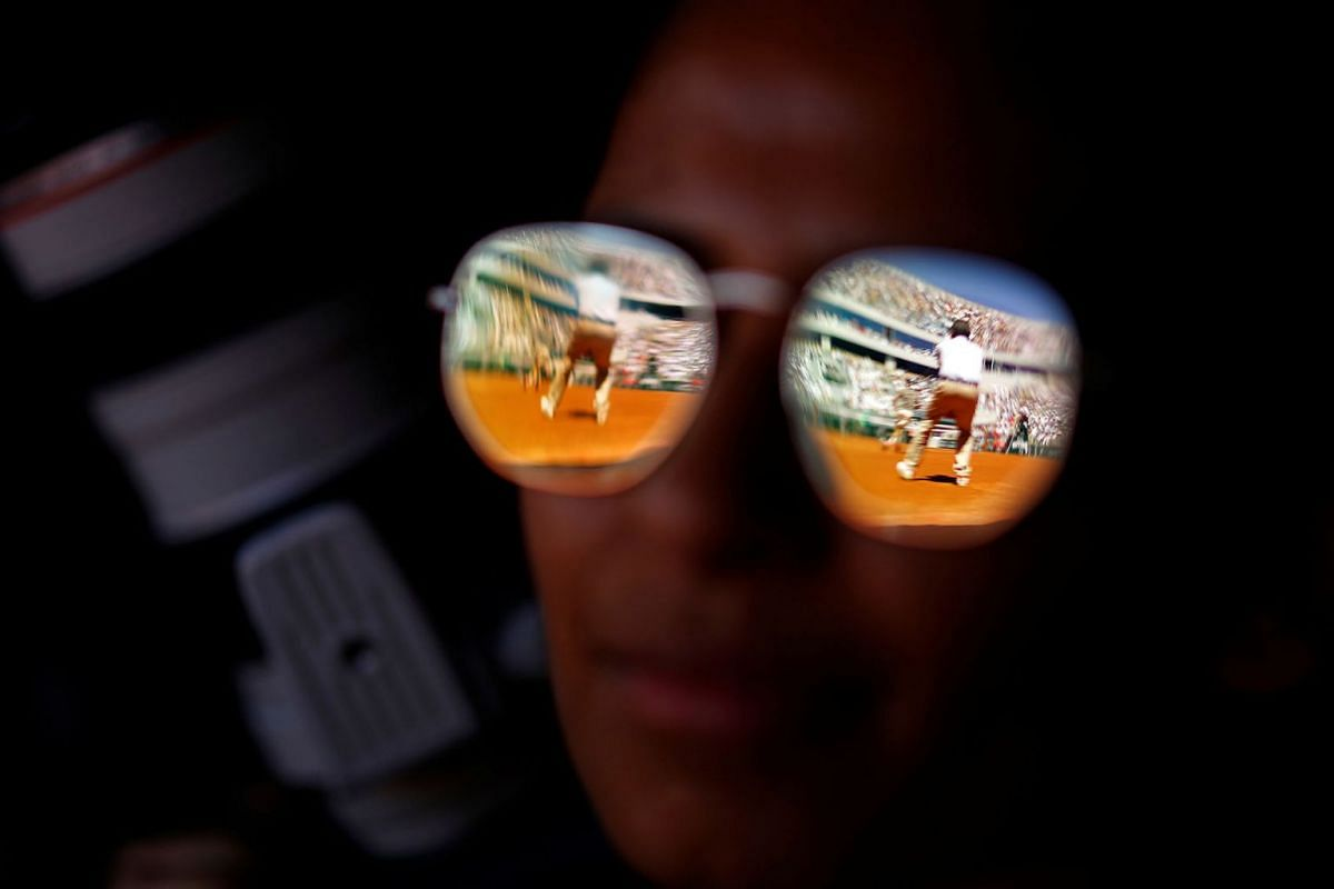 A spectator watches the fourth round match in the French Open played in Paris, France, between Switzerland's Roger Federer and Argentina's Leonardo Mayer, June 2, 2019.