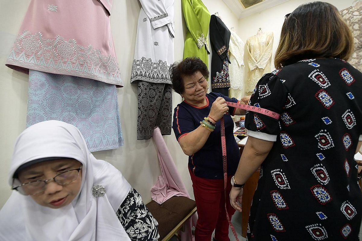 Ms Chua uses a whiteboard to help Madam Lie keep track of the customised orders, while Madam Lie takes a customer's measurements (above). Orders for Hari Raya can come in as early as six months before the festival.