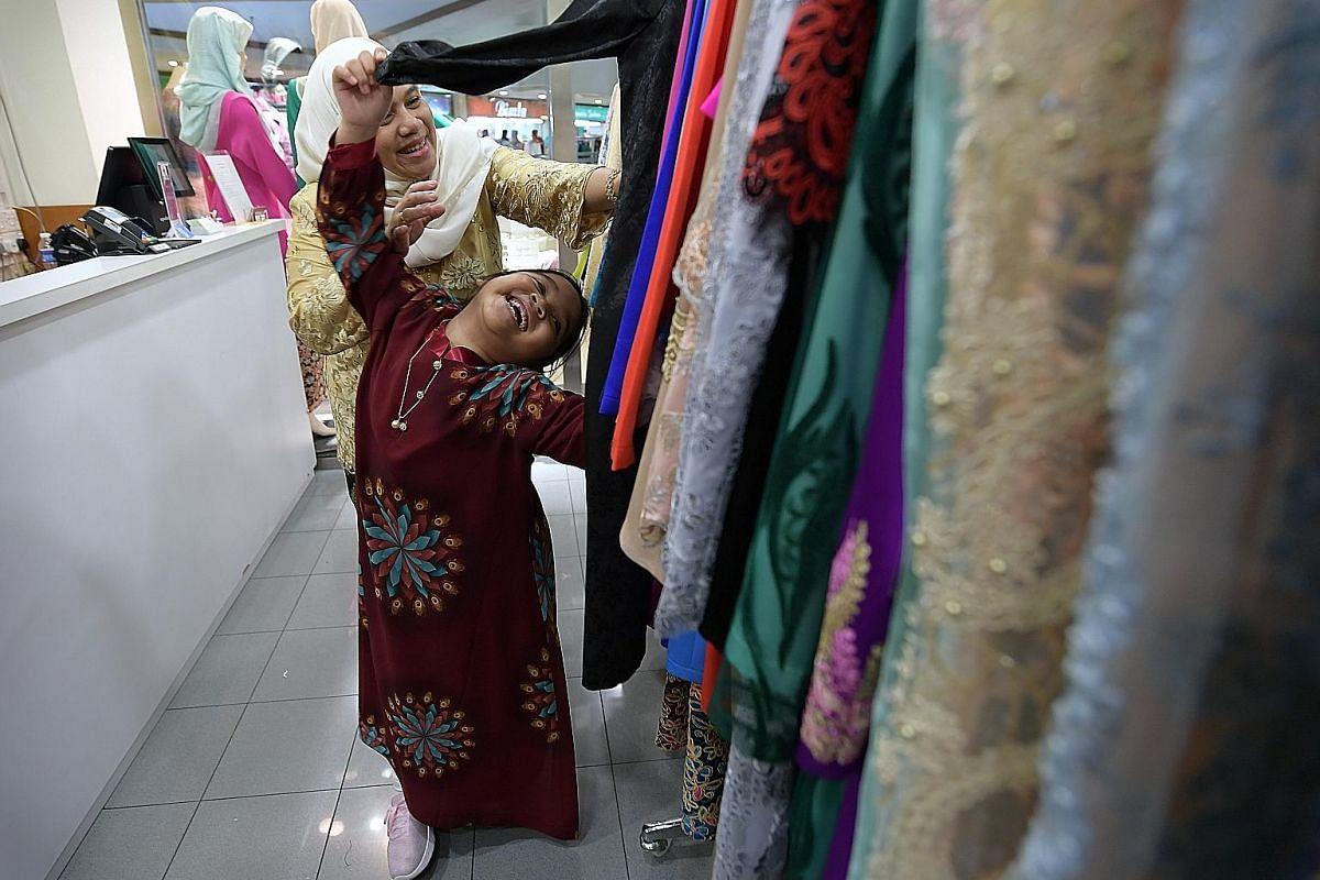 Melati, six, playing among the colourful row of clothing at Bewa Enterprise while her mother Diah Hastuti Pangestu Sagala, 46, browses.