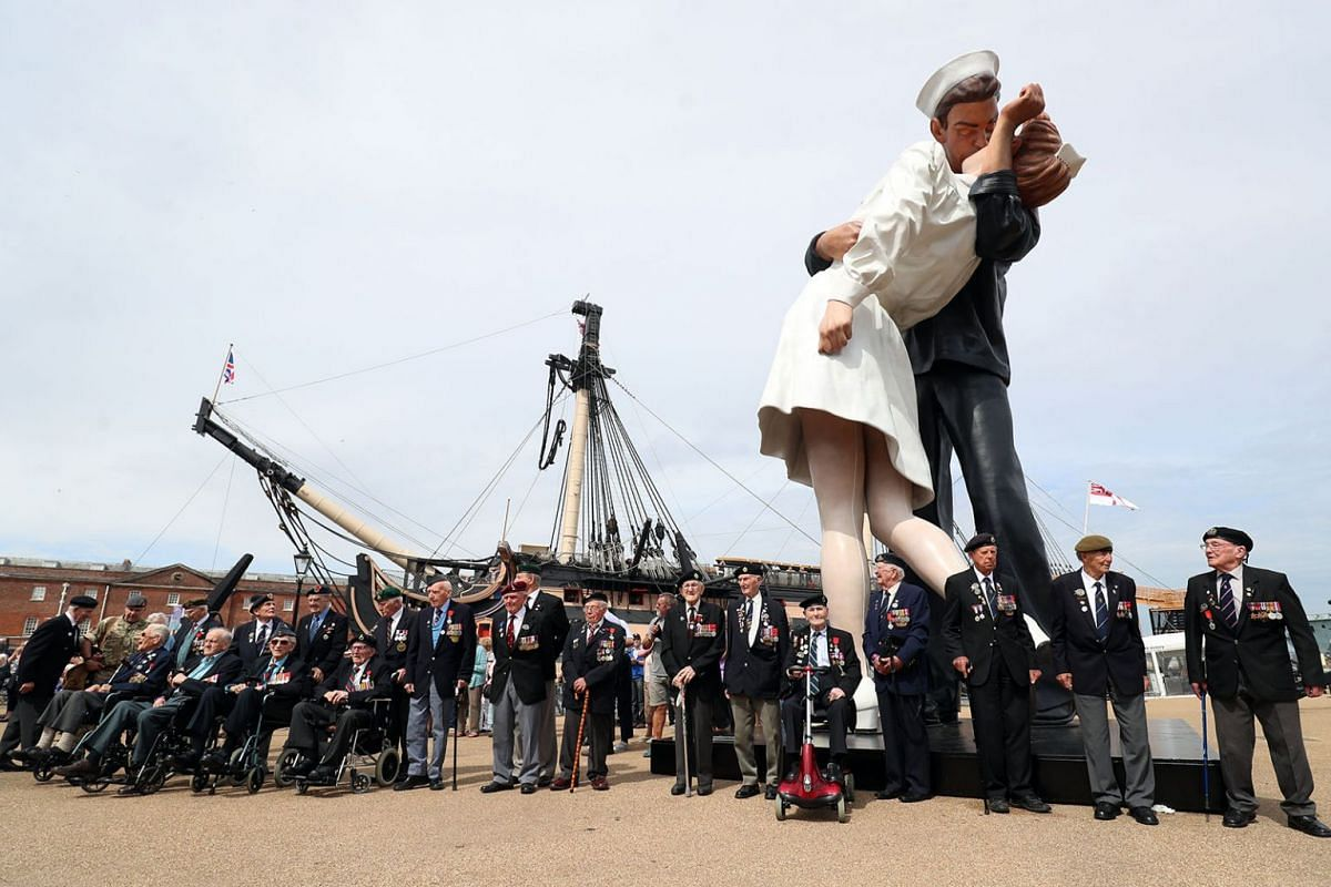 D-Day veterans stand under the 'Embracing Peace' statue during the celebrations of the 75th anniversary of the landing of allied troops in Normandy during World War II (D-Day), at Portsmouth Historic Dockyard, England, June 2, 2019,