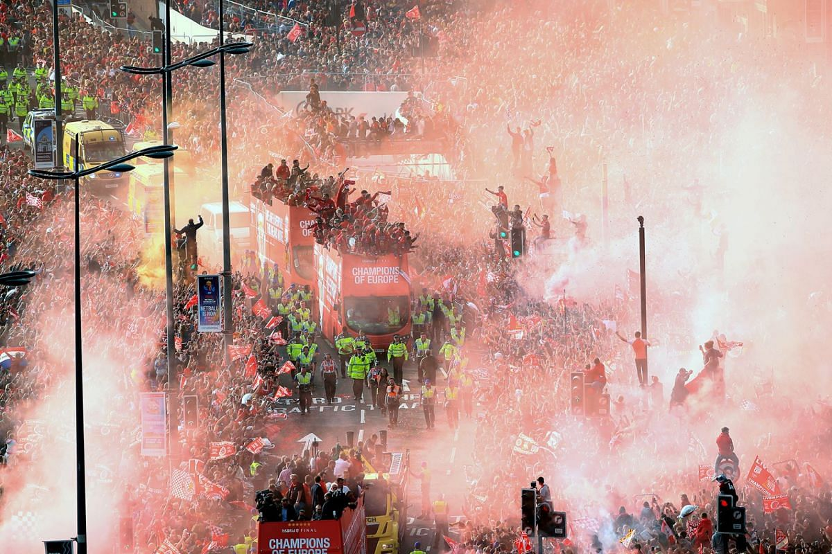 Liverpool players celebrate in an open top bus with fans during the Champions League Winners Parade in Liverpool, England, June 2, 2019, a day after they won the UEFA Champions League final soccer match against Tottenham Hotspur.