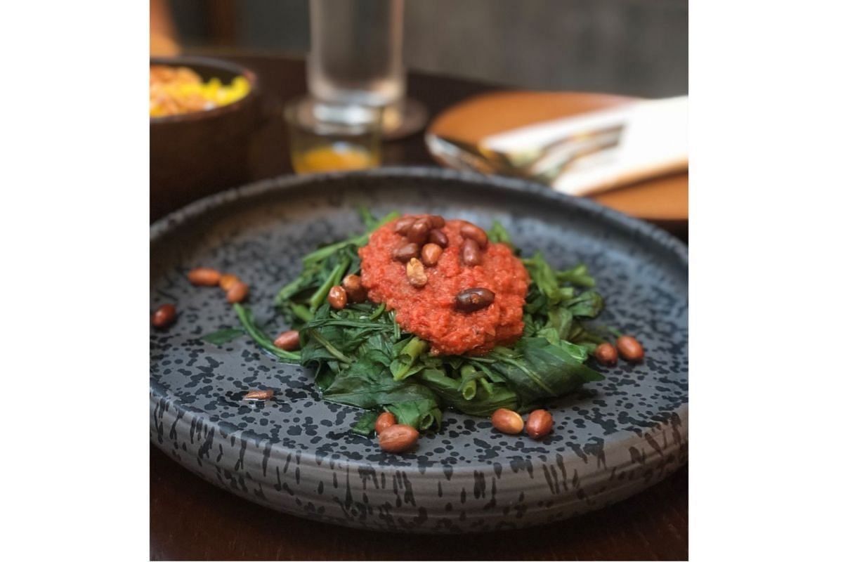 Plecing Kangkung is steamed kangkong topped with tomato chilli sambal and roasted peanuts.