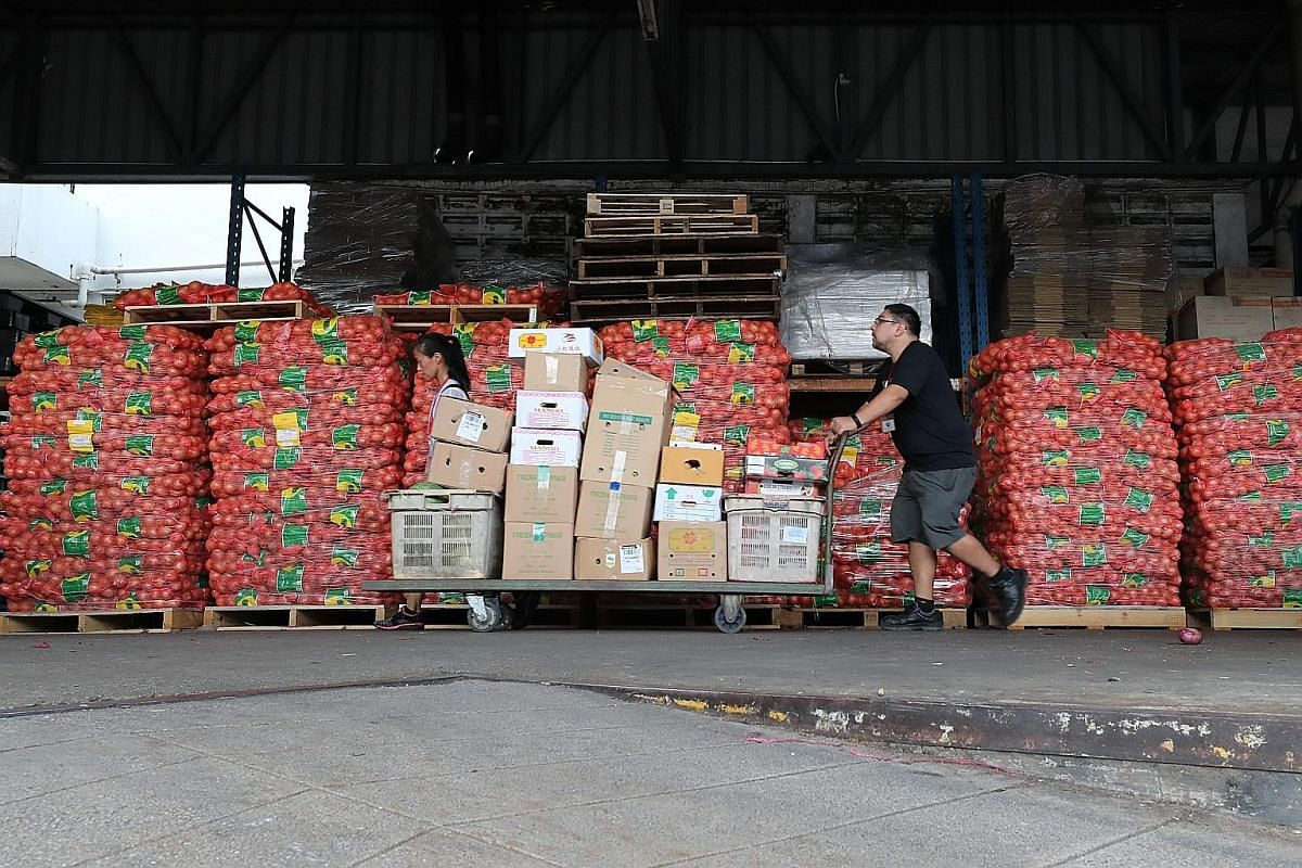 Boxes of fruits and vegetables that are sorted and ready for volunteer drivers to pick up and deliver to local charities. Within an hour, volunteers can collect more than 1,000kg of food at the wholesale market. Volunteer Nicolas Theodoru pushing a t