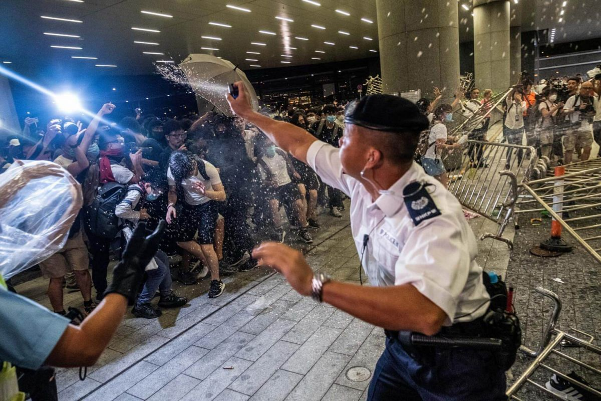 A police officer uses pepper spray on demonstrators during a protest in Hong Kong, on June 10, 2019.