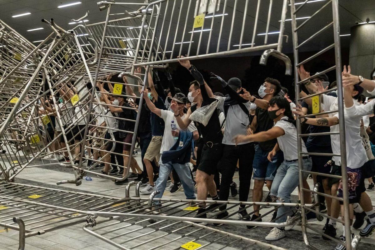 Demonstrators push metal barriers during a protest in Hong Kong, on June 10, 2019.