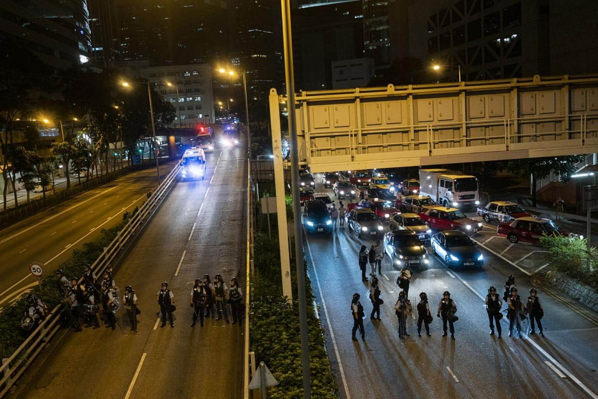Police officers in protective riot gear stand guard in front of vehicles as demonstrators block Gloucester Road during a protest against a proposed extradition law in Hong Kong, in the early hours of June 10, 2019.