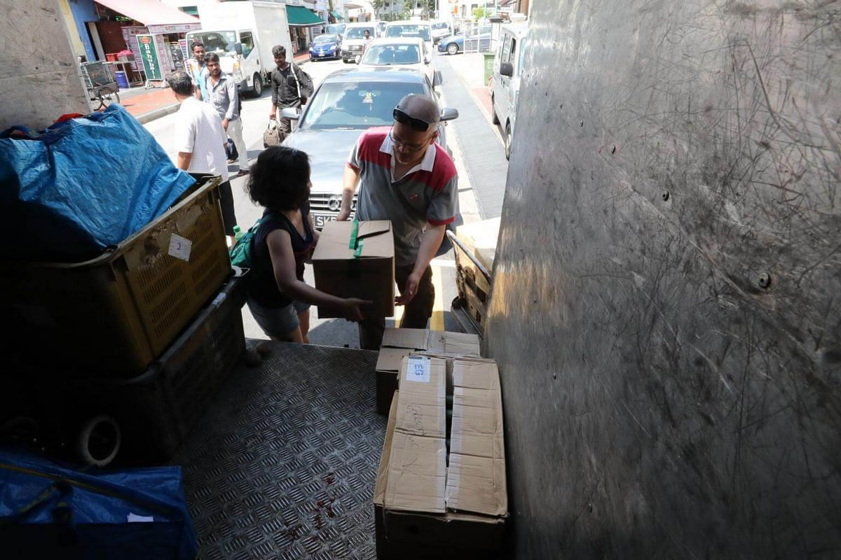 Volunteers unloading cartons of fruits and vegetables at Krishna's Kitchen, one of the charities that SG Rescue supports.