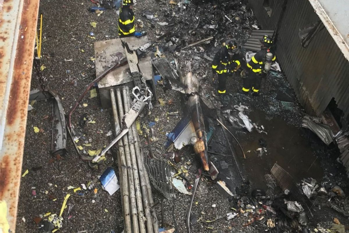 A photo provided by the New York Fire Department shows the charred remnants of a helicopter on part of a rooftop of 787 Seventh Avenue in Manhattan on Monday, June 10, 2019. Officials said the pilot, who was killed, was the only person aboard the air