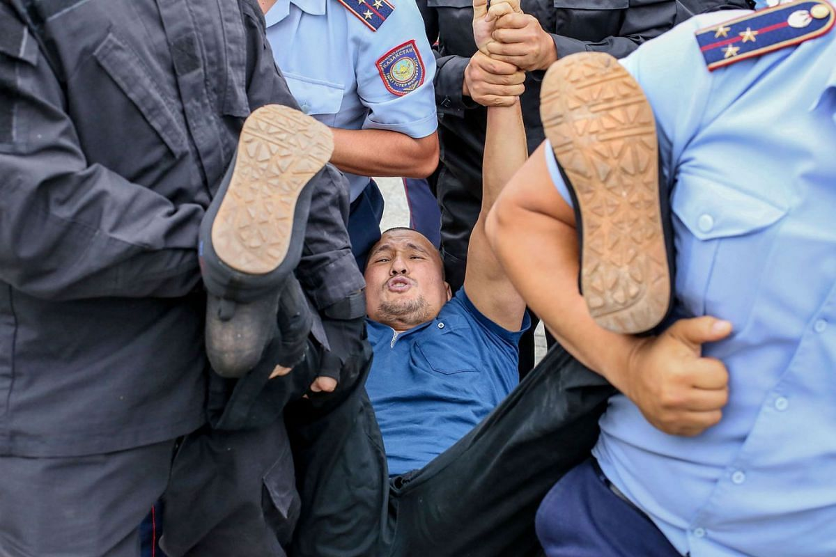 Police officers detain an opposition supporter on June 10, 2019 in Almaty, a day after Kazakhstan's presidential elections. PHOTO: AFP