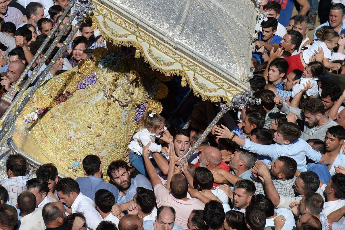 People touch an effigy the Rocio Virgin during a procession at the village of El Rocio on June 10, 2019. PHOTO:  AFP