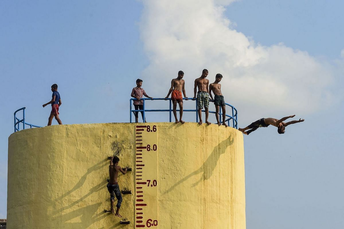 Bangladeshi youths jump into the Buriganga River during a hot summer day in Dhaka on June 10, 2019. PHOTO: AFP