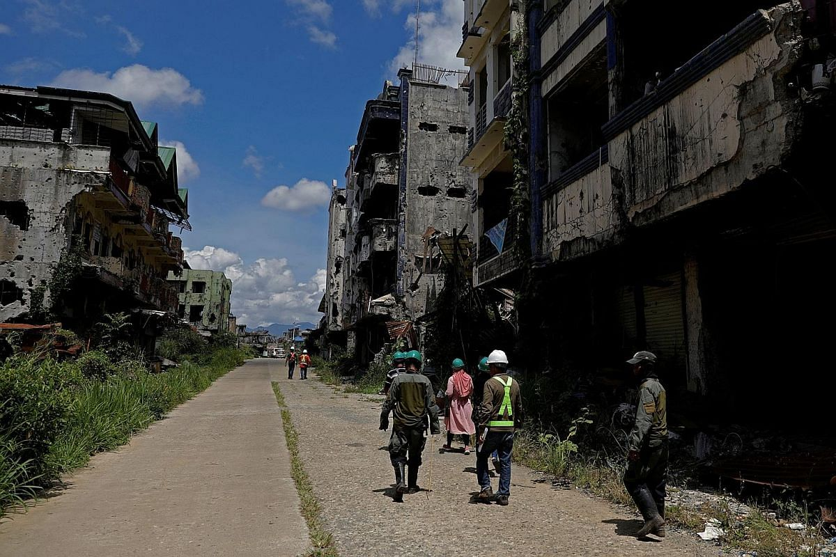 Internally displaced people walking with safety managers during a visit to the war-torn area of Marawi City last month. They have to agree to have their wrecked homes demolished before rebuilding can start. An evacuation camp in Marawi City. The gove