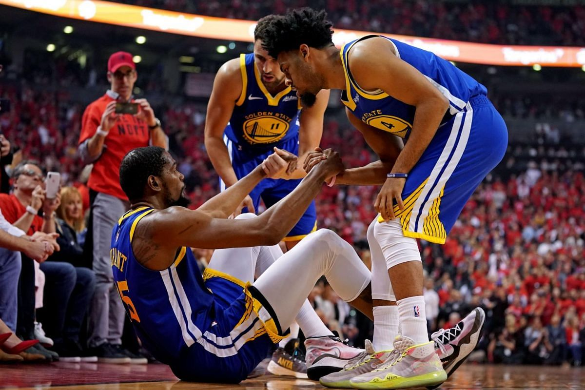 Golden State Warriors forward Kevin Durant (35) is helped up by guard Quinn Cook (4) and guard Klay Thompson (11) after an apparent injury during the second quarter in Game 5 of the NBA Finals against the Toronto Raptors at Scotiabank Arena in Toront