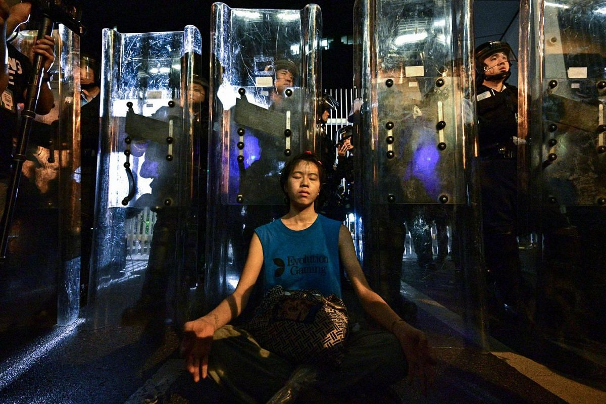 A woman (C) meditates in front of a line of riot police standing guard with their shields outside the government headquarters in Hong Kong early on June 12, 2019, three days after the city witnessed its largest street protest in at least 15 years as