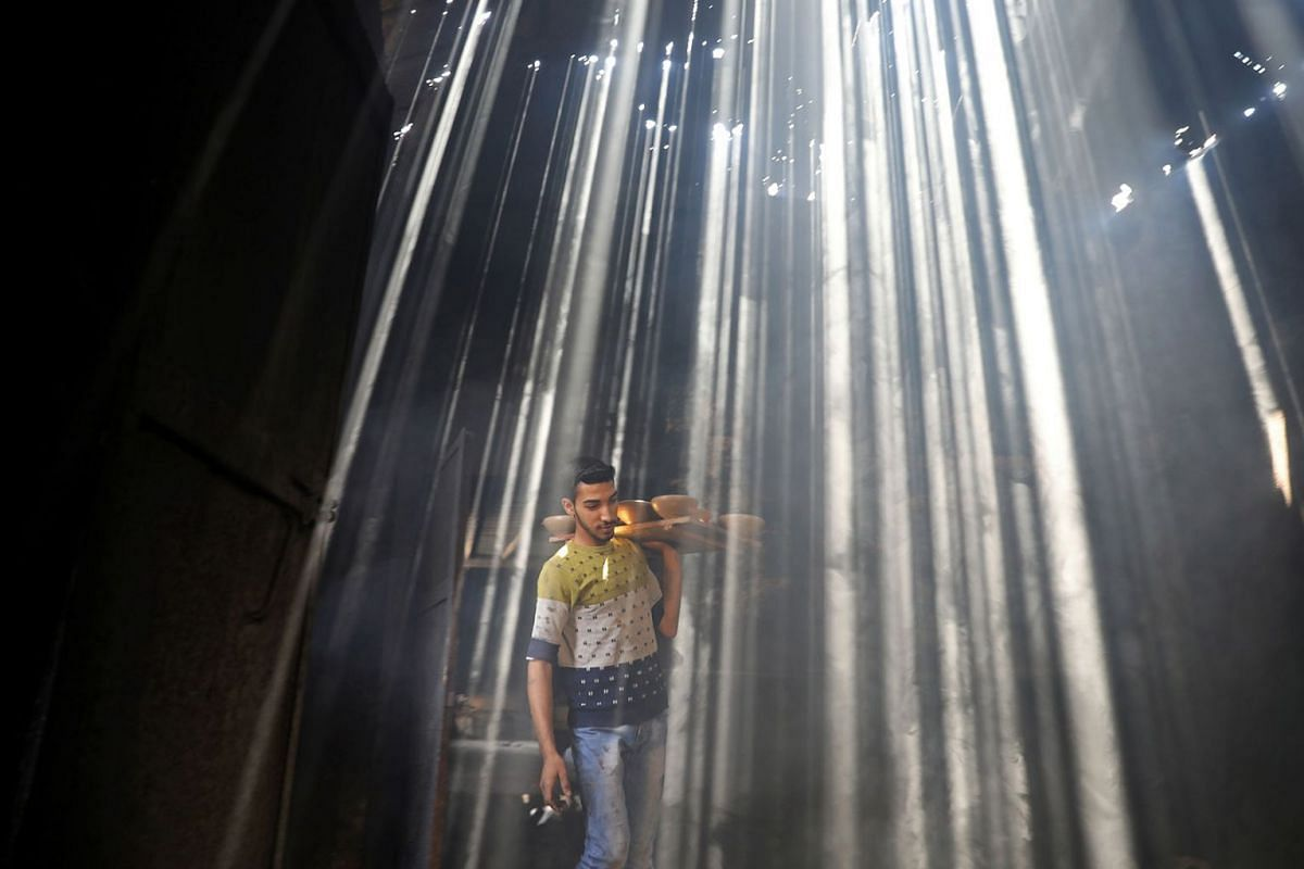 A Palestinian worker carries clay pots as the sun rays penetrate through the ceiling of a pottery workshop in Gaza City June 11, 2019. PHOTO: REUTERS