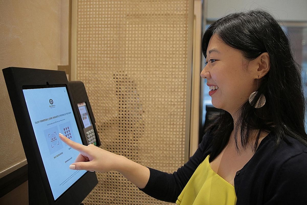 Straits Times tech video producer Bryan De Silva trying the self-check-in system at Swissotel The Stamford. (Left and below left) Straits Times tech correspondent Yip Wai Yee testing the facial recognition technology at coffee chain Old Town White Co