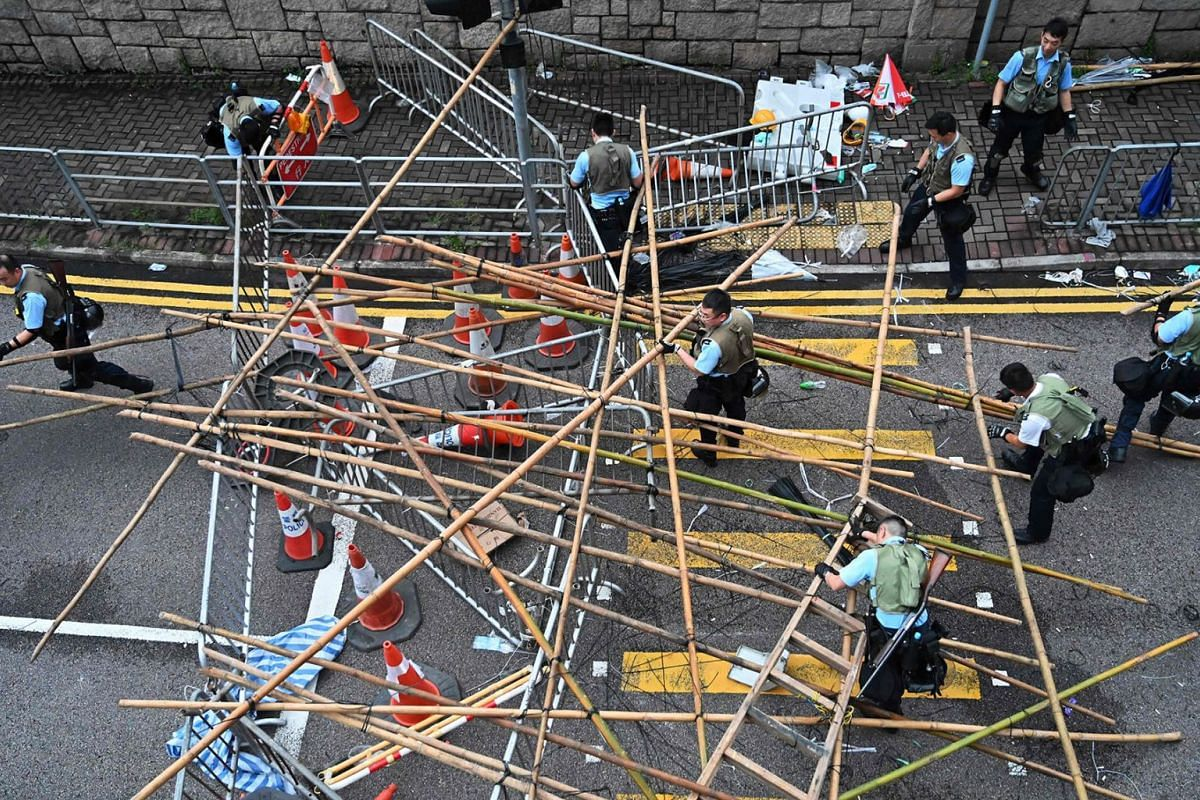 Police officers dissolve the barricades placed by demonstrators in Hong Kong on June 12, 2019. - Violent clashes broke out in Hong Kong on June 12 as police tried to stop protesters storming the city's parliament, while tens of thousands of people bl