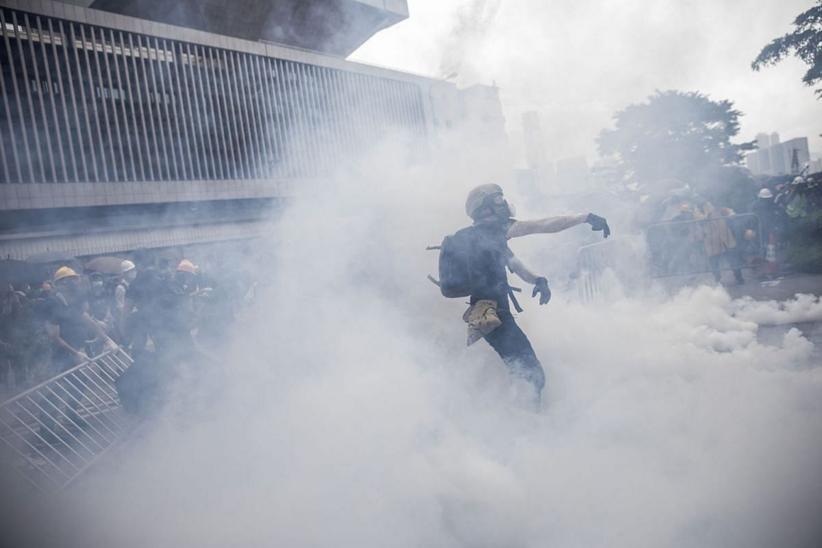 A protester stands in a cloud of tear gas during a protest against a proposed extradition law in Hong Kong, China, on Wednesday, June 12, 2019. Protesters flooding downtown Hong Kong to stop the government's proposed extradition law effectively prese