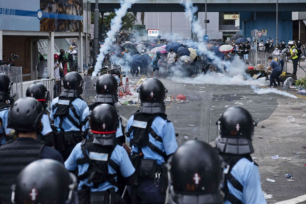 Police officers fire tear gas towards protesters during a protest against a controversial extradition law proposal, outside Hong Kong's government headquarters on June 12, 2019. PHOTO: DPA