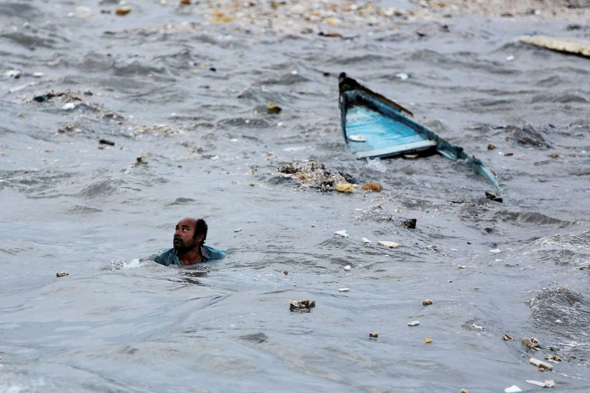 A fisherman swims to shore after his boat capsized due to high waves ahead of the expected landfall of Cyclone Vayu at Veraval, India, June 12, 2019. PHOTO: REUTERS