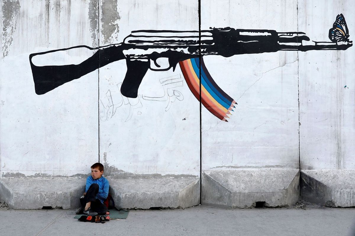 A shoe polisher waits for customers under graffiti on a wall in Kabul, Afghanistan June 13, 2019. PHOTO: REUTERS