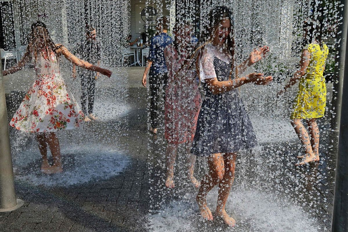 Children play under showers that are part of a public fountain to cool off on June 13, 2019 in Vilnius, where temperatures rose up to 35 degrees Celsius. PHOTO: AFP