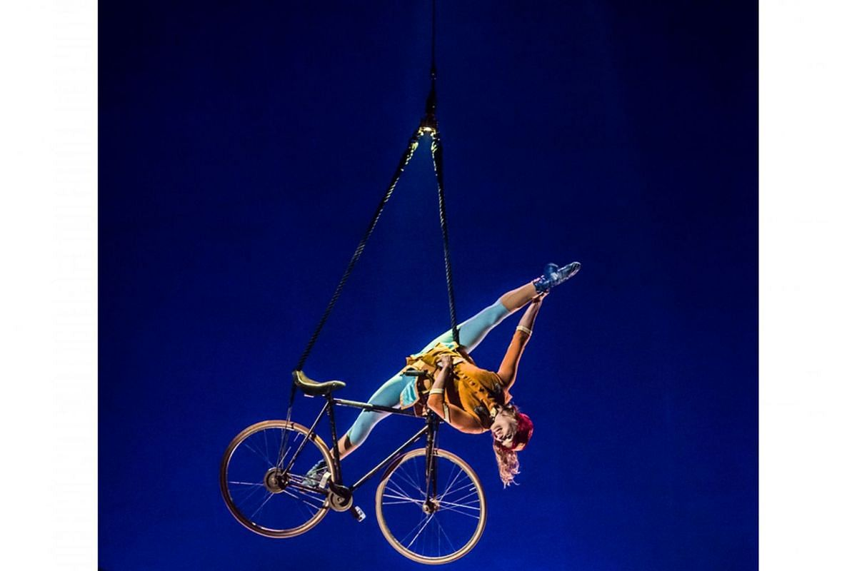 Some of the death-defying acts include the Aerial Bicycle (above), where a girl dangles on a bike in the air; the Upside Down World, where a man is perched on the back of a chair atop a pile of chairs; and the Rola Bola act, where an acrobat balances on a
