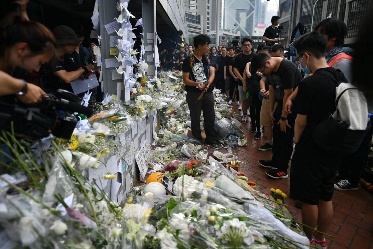 Bouquets of white flowers, written tributes and origami cranes outside Pacific Place, Hong Kong, on June 16, 2019.