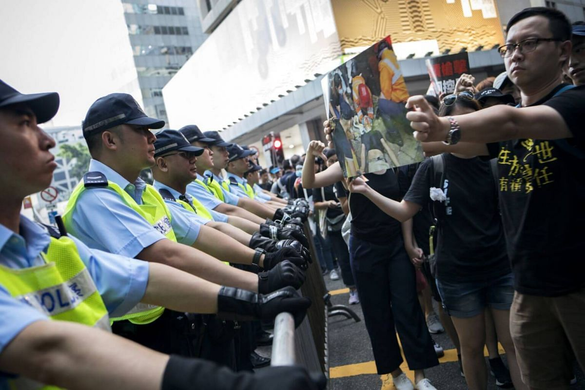 Police officers stand guard as protesters march past the police headquarters during a rally in Hong Kong, on June 16, 2019.