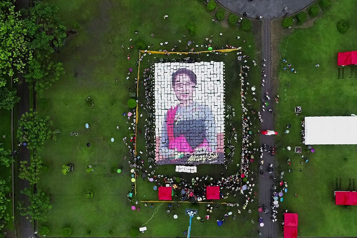 This aerial handout picture taken and provided on June 19, 2019 by one of the event organizers, Tharr Zaw, shows supporters making a mosaic portrait of Myanmar State Counsellor Aung San Suu Kyi with placards during an event to celebrate her 74th birt