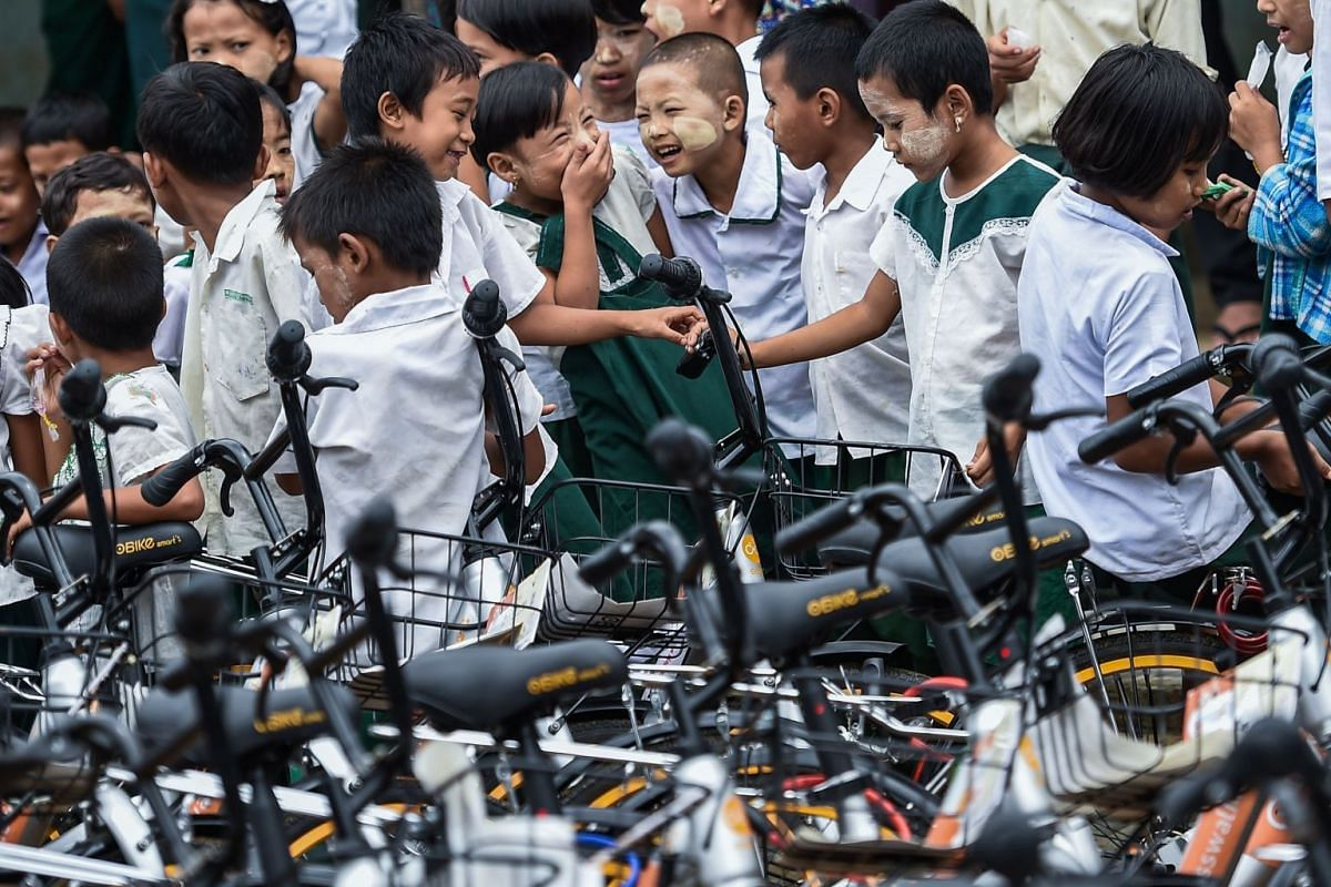 Students look bicycles at a school on the outskirts of Yangon, on June 18, 2019.