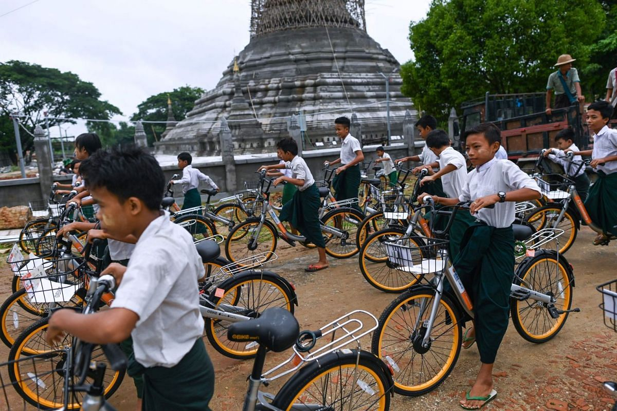 Students ride bicycles which have been donated as part of the Lesswalk scheme, on the outskirts of Yangon, on June 18, 2019.