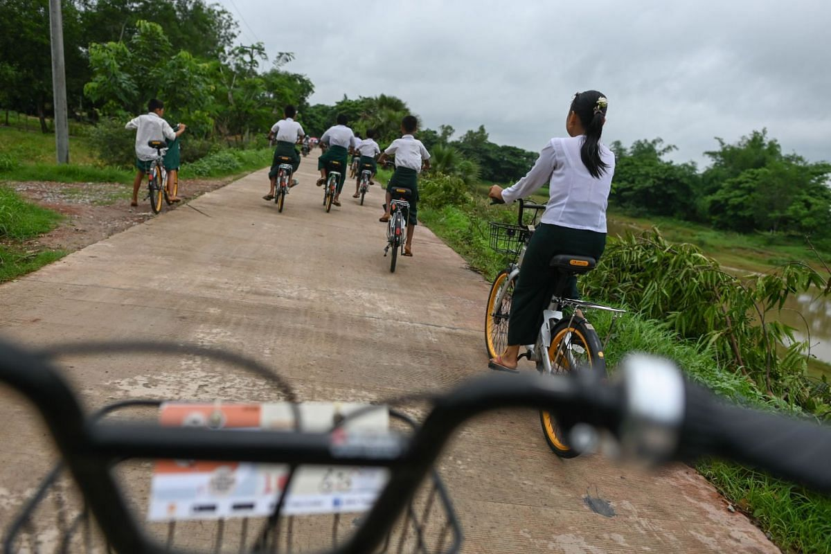Students ride bicycles on the outskirts of Yangon, on June 18, 2019.