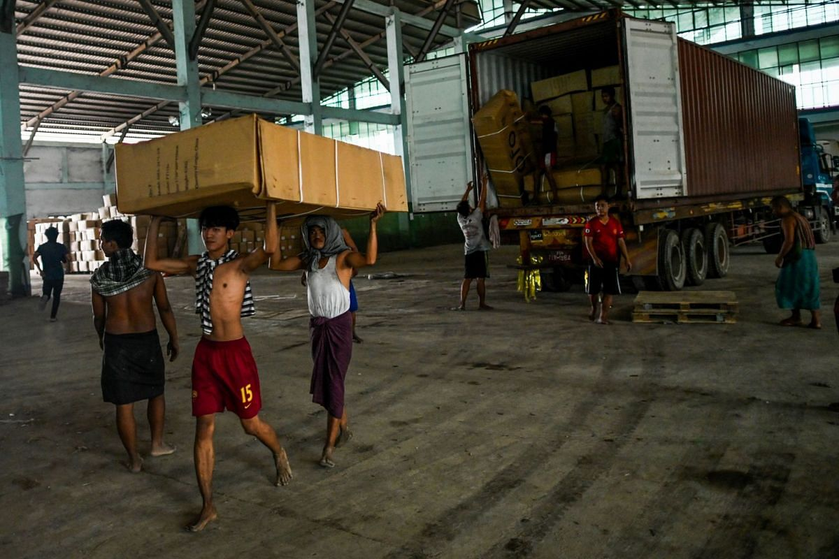 Workers unload bicycles at a warehouse in Yangon, on June 15, 2019.