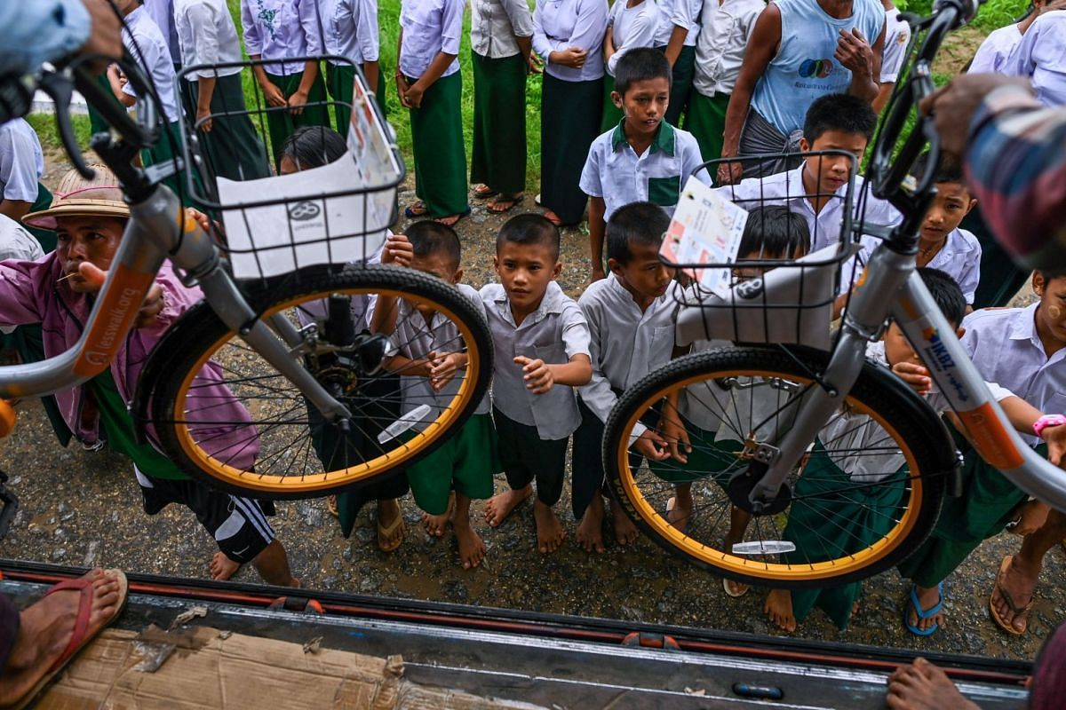 Students help unload bicycles on the outskirts of Yangon, on June 18, 2019.