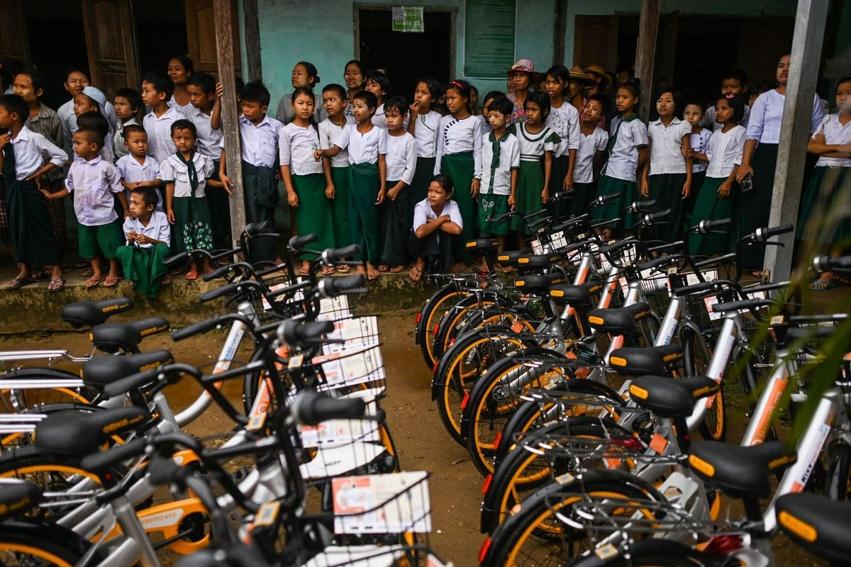 Students look at bicycles at a school on the outskirts of Yangon, on June 18, 2019.