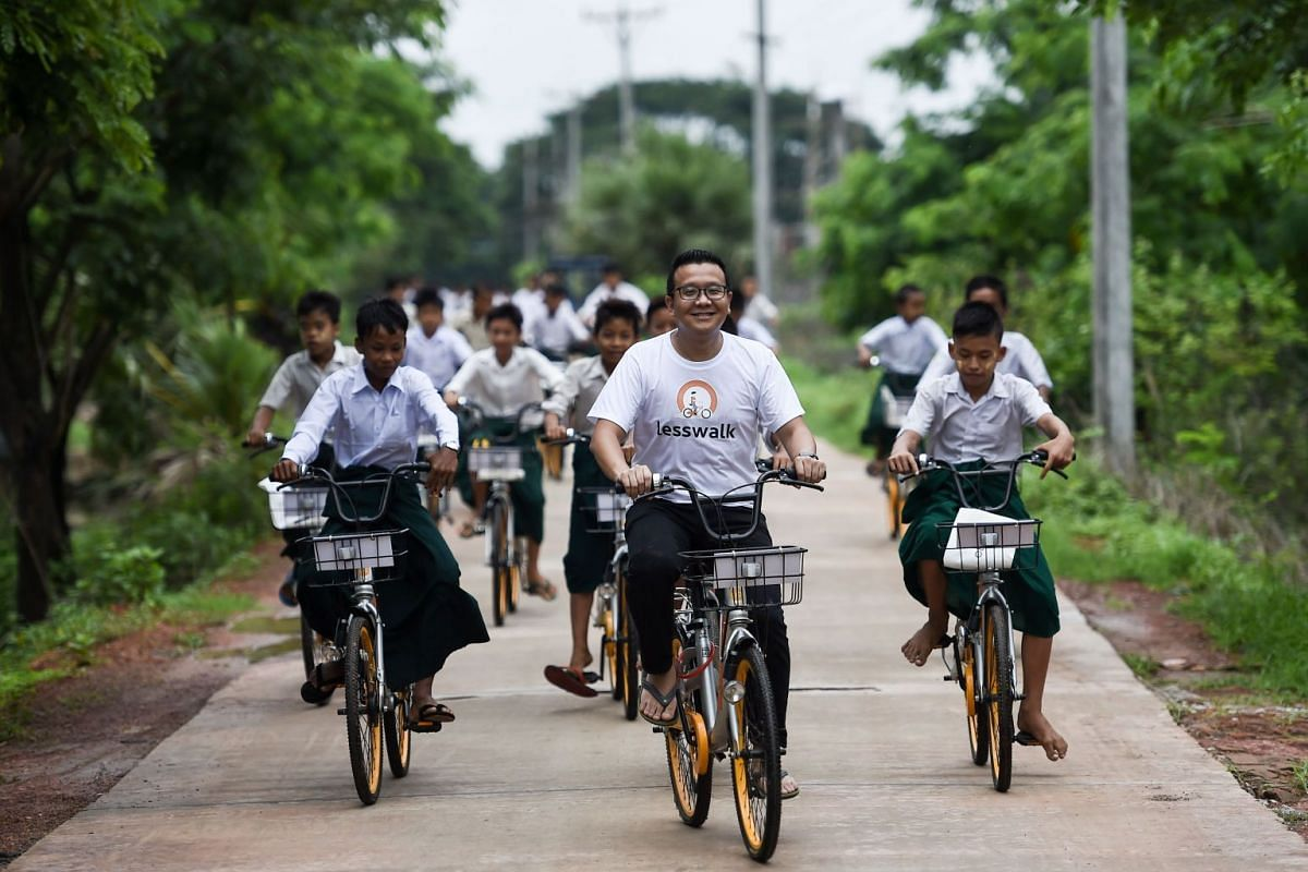Mike Than Tun Win (centre) cycles with students on bicycles on the outskirts of Yangon, on June 18, 2019.